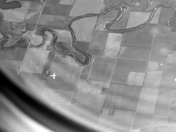 Airliner Under Airliner Over Farms bw -© 2012- photo by Max Clarke